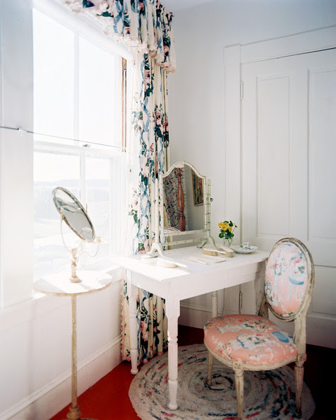 Bedroom - A white vanity and an upholstered chair set beside a window with floral curtains