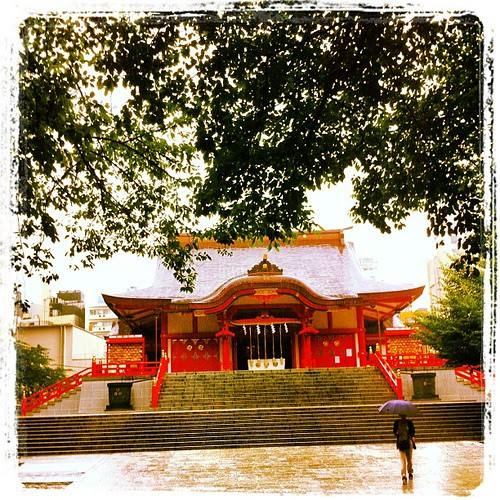 I am standing in front of Hanazono Shrine while it rains heavily.