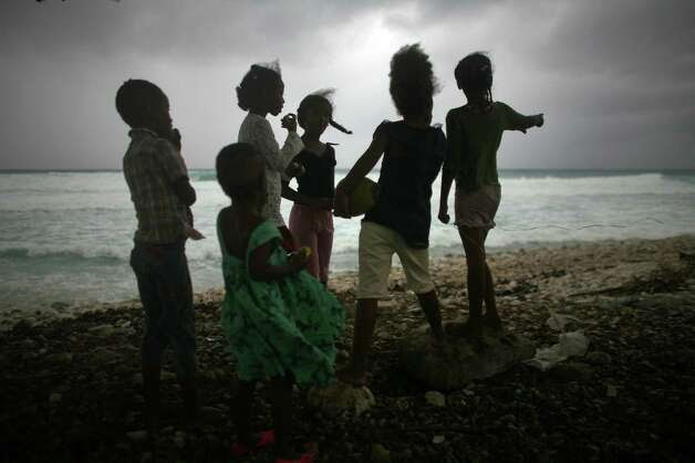 Children look for the approach of Tropical Storm Isaac on a beach in Barahona, Dominican Republic on Friday. Isaac strengthened slightly but will not likely become a hurricane until it enters the Gulf of Mexico. Photo: Ricardo Arduengo / AP