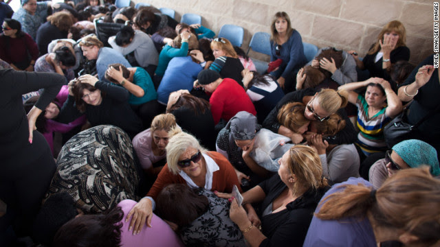 People take cover during a rocket attack at a funeral Friday in Kiryat Malakhi, Israel.