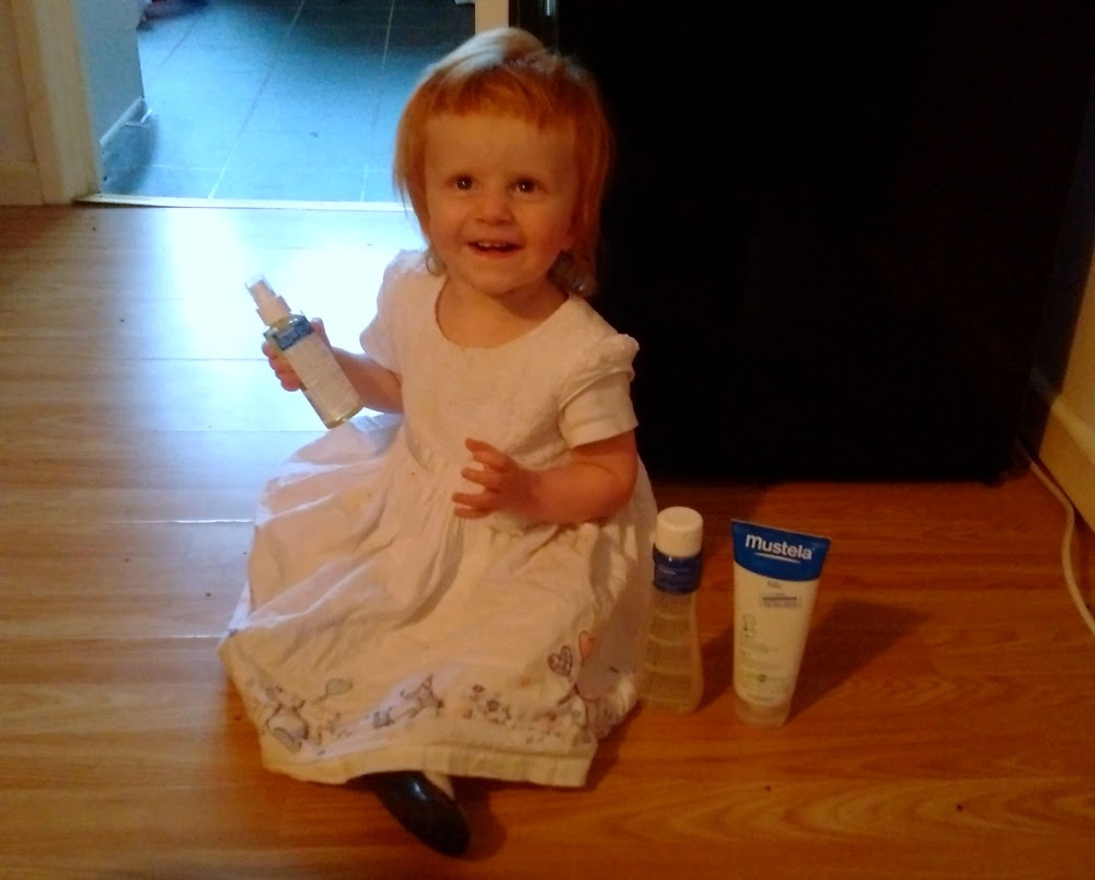 Marianna with bottles of Mustela skin care