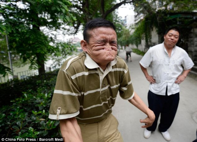 Taking the strain: Tang, pictured in Chengdu, China, contorts his face and body to create the ugly spectacle