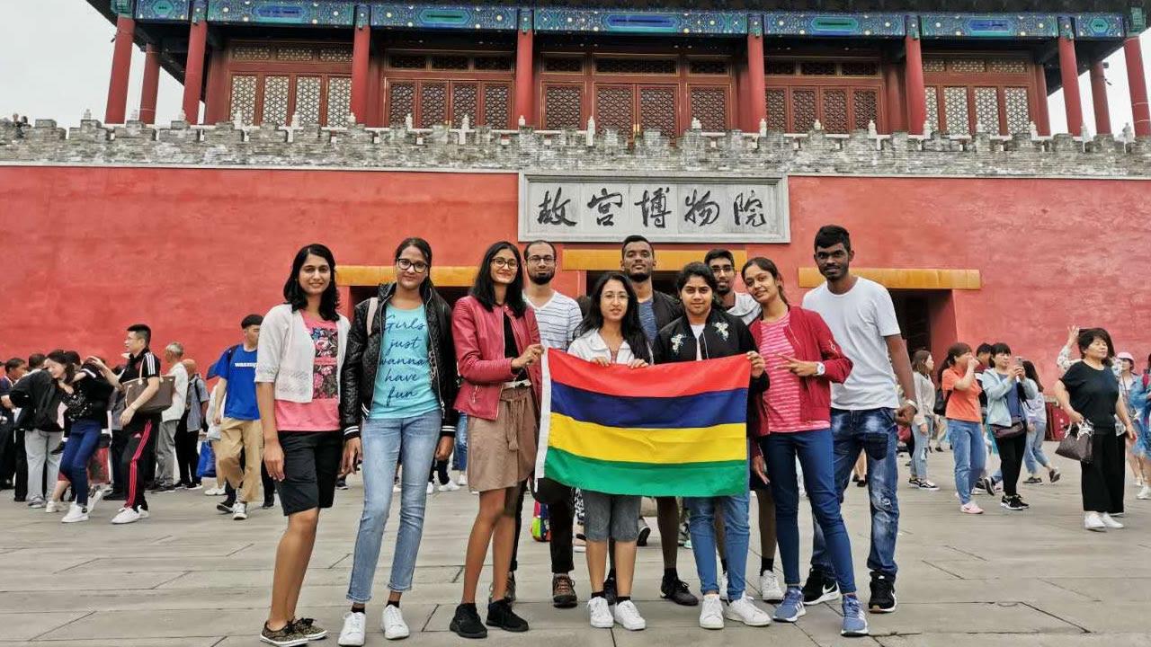Les étudiants Mauriciens posent fièrement avec le drapeau Mauricien devant le Zheng Yang Men.