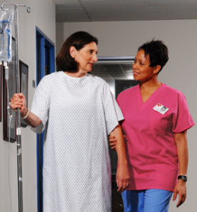 Woman in hospital gown with IV pole walking in hospital hallway with healthcare provider.