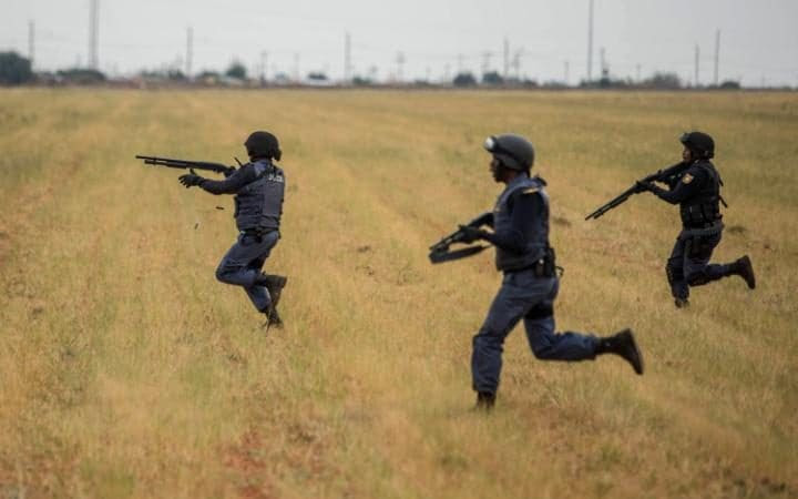 South African riot police officers run to disperse protesters in Coligny