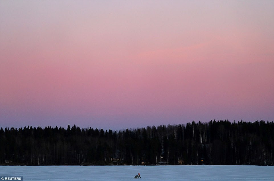 A woman pushes a pram as she walks over a frozen lake during sun down at the Pajulahti sports center near Lahti, Finland, on February 21