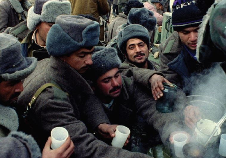 AZERI SOLDIERS crowd around a pot to get some hot tea on the front line between Nagorno-Karabakh gue