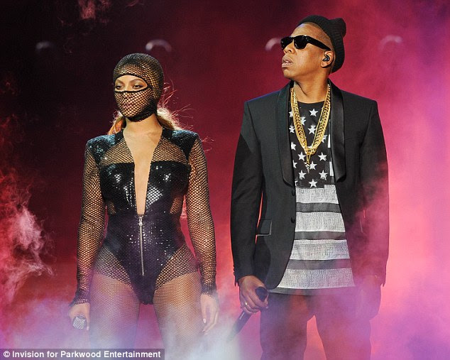 Looking cool: Jay-Z, 44, sported a black blazer over a shirt emblazoned with the US flag, along with gold chain necklaces, and a black beanie