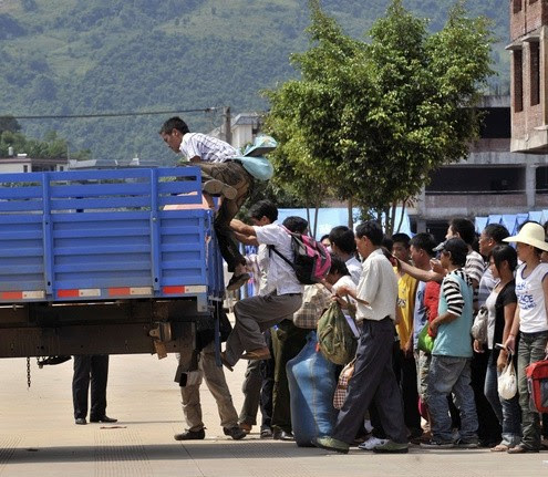 Refugees board a vehicle as they return to Myanmar from the border town of Nansan, China's Yunnan province