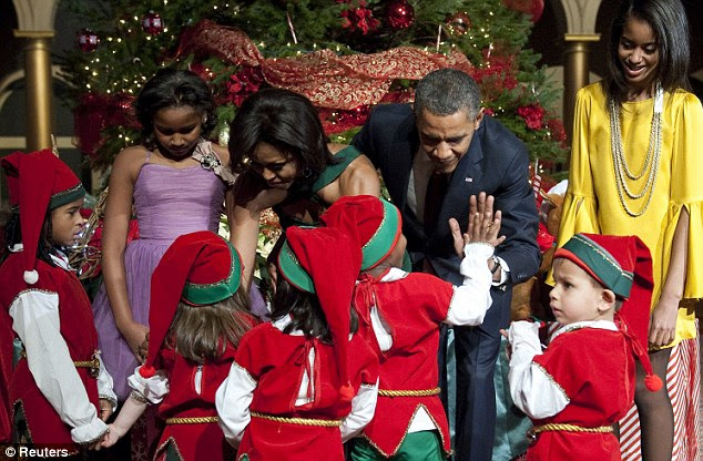 The most wonderful time of the year: President high-fives a young patient as they excitedly crowd round the Obamas at the carol concert in the National Building Museum