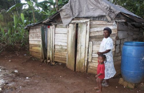 Rosemie Durandisse stands with one her children in front of her temporary home. / Credit:Fritznelson Fortuné/IPS
