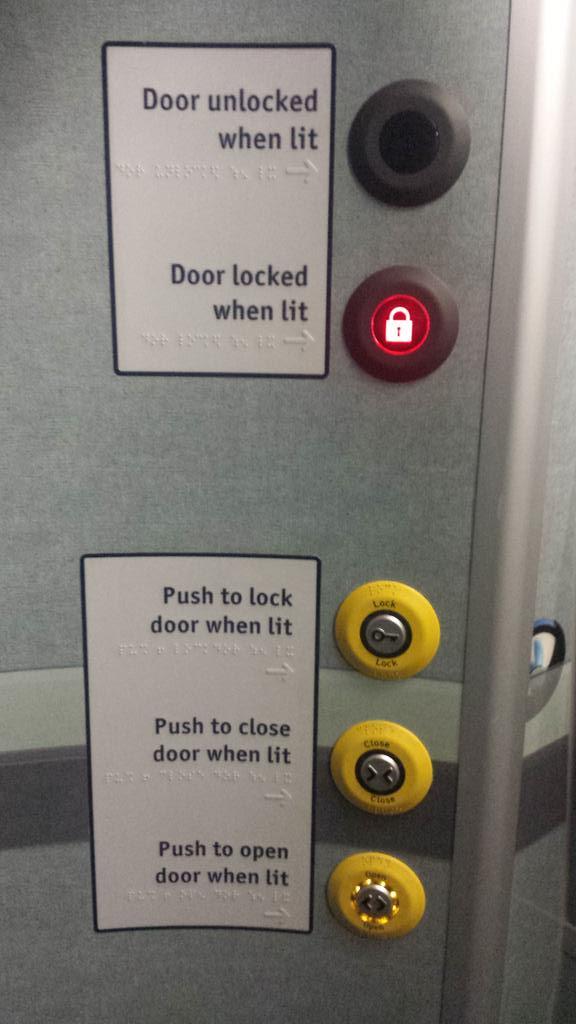 Indicadores luminosos para saber si una puerta está bloqueada o no y pulsadores iluminados para poder abrir y cerrar con los letreros traducidos al braille, cuando no sirve para nada sin ver los indicadores.