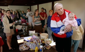 **CORRECTS LAST NAME TO ROPER ** ** ADVANCE FOR SUNDAY, JUNE 4 **Pastor Fred Phelps, right, holds his great-granddaughter, Zion Phelps-Roper, as he sings happy birthday to family members during a gathering at the Westboro Baptist Church in Topeka, Kan. April 9, 2006. Phelps and his tight-knit congregation travel the country preaching damnation to a nation of sinners. (AP Photo/Charlie Riedel)