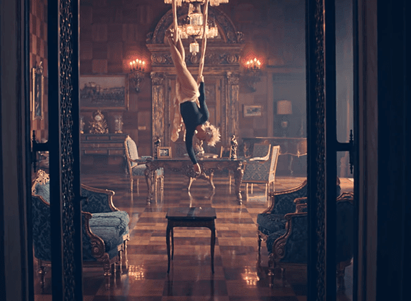 Pink is upside down and spinning inside a lavishly decorated room.