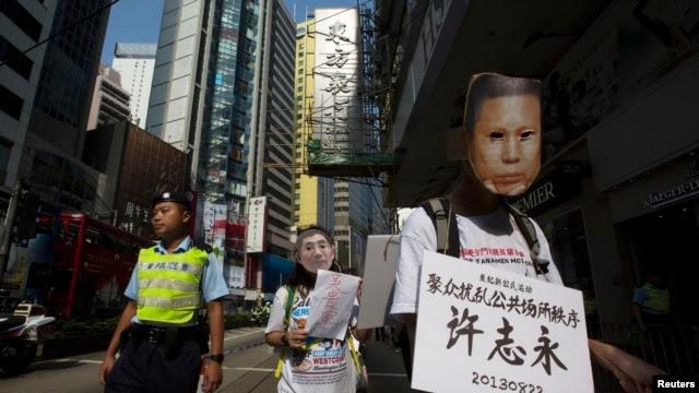 香港民主派抗议者戴着象征许志永的面具在香港街头抗议,要求中国释放政治犯。(2013年10月1日)
