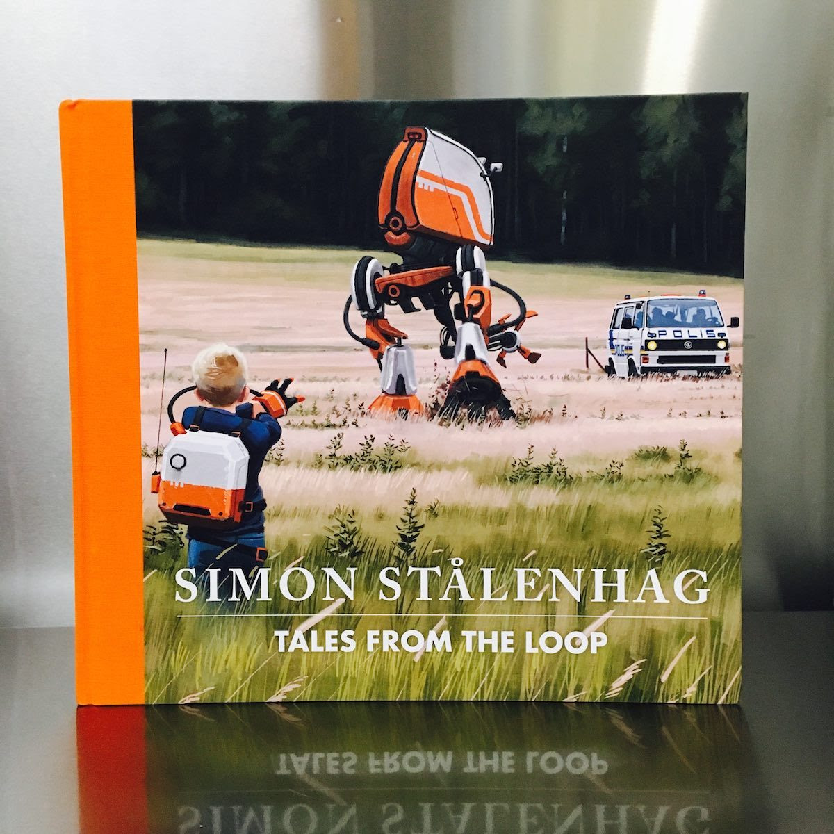 """Tales from the Loop – An eerie account of a physics research facility gone awry  Tales from the Loop  by Simon Stålenhag  Design Studio Press  2015, 128 pages, 10.1 x 11.2 x 0.7 inches  $33  Buy a copy on Amazon  Unfamiliar with sci-fi artist Simon Stålenhag, I was sucked into his eerie dystopian history the instant I cracked open Tales from the Loop. His hyper-real digital paintings depict beautiful Swedish country towns where snow falls in the winter and children play in nature. But each of these pastoral scenes are jarring, with intrusive machines, robots, discarded equipment, and power lines upstaging the otherwise serene landscape.  The book explains that these paintings were inspired by childhood memories of the author, who grew up in a large area of Sweden that housed an underground experimental physics research facility known as The Loop. Alongside each painting is a short essay from the author's memory. For instance, the three cooling towers in the photo above were built to release heat from the core of the Loop. The towers, which """"started like a deep vibration in the ground that slowly rose to three horn-like blasts,"""" remind Stålenhag of a miserable day he had with a boy named Ossian, who had lured him to his house to play Crash Test Dummies, but ended up bullying him with the help of his brother until Stålenhag went home in tears.  Each painting is accompanied by one of these short yet captivating stories, and their detailed, relatable quality had me going. As I read about Stålenhag and his best friend Olof sneaking off with a boat on a nice summer day to a disturbing machine-littered swimming pond, I kept thinking, """"I must go online and research the Loop! How could I have never heard about this creepy place?"""" Then I quickly got to the robots. Huge dinosaur and prehistoric animal robots. And towering two and four-legged machine robots, crushing everything in their paths. Suddenly, with a """"Wait a minute!"""" moment, I knew I'd been had. The same way I was dup"""