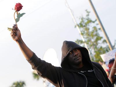 Un manifestante levanta una rosa para pedir justicia por Martin.