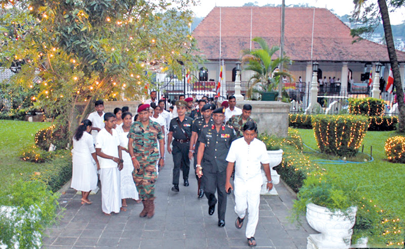 Army Commander Lieutenant General Mahesh Senanayake and other military officials entering the temple premises.