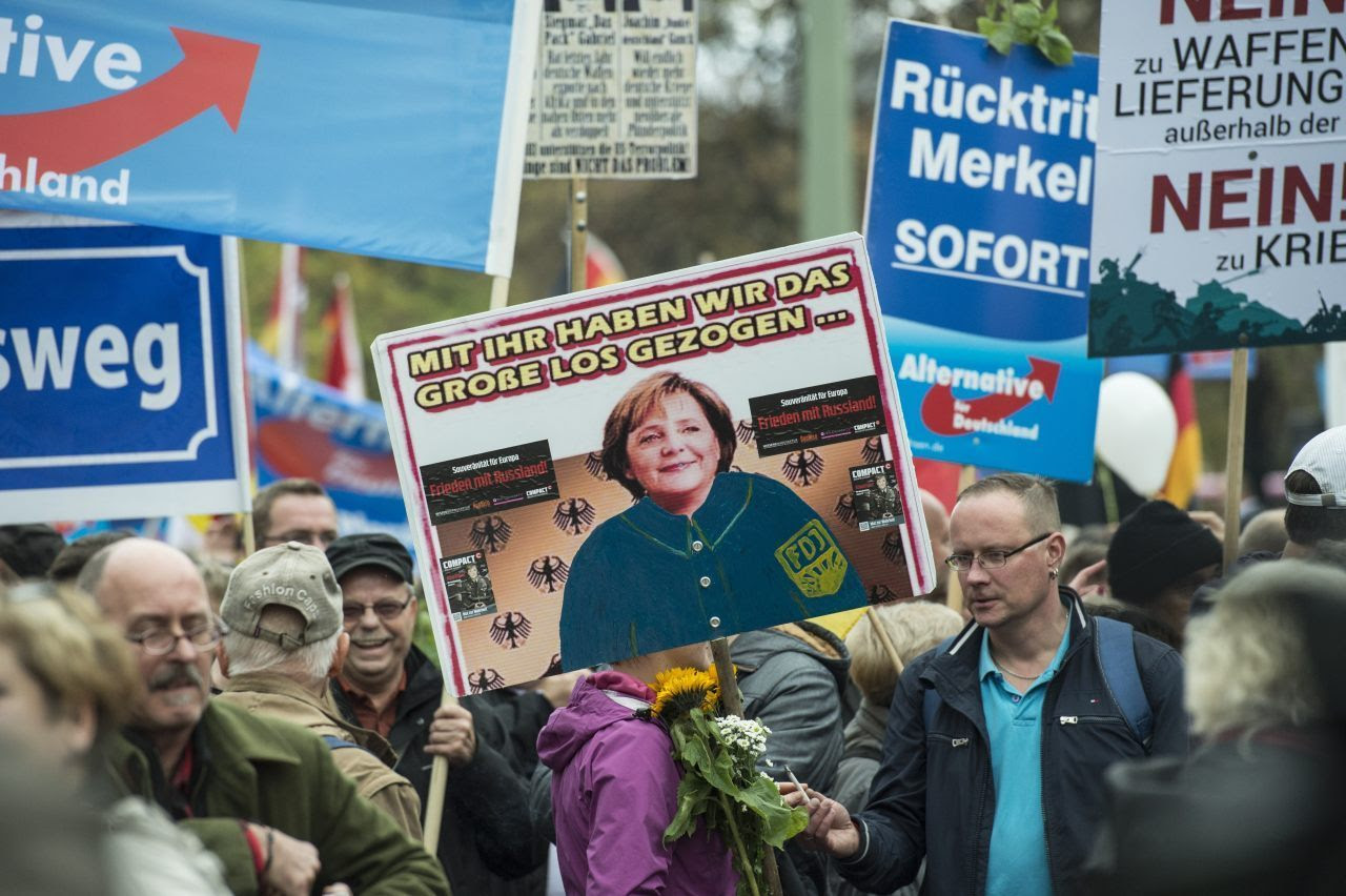 """An AfD supporter holds a placard depicting Angela Merkel wearing the uniform of the old Communist """"German Free Youth"""". The text says: """"With her we have hit the jackpot..."""" (JOHN MACDOUGALL/AFP/Getty Image)"""