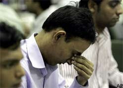 A stock broker reacts after watching the BSE index tumble on his trading terminal.