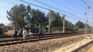 Usuaris de l'R16 caminant per la via del tren