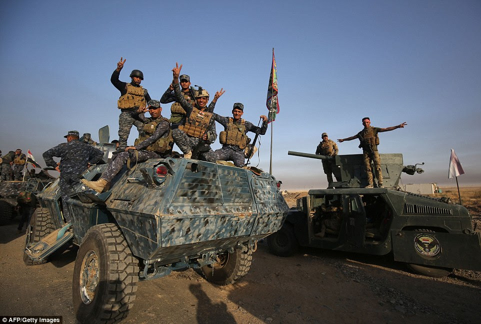 Iraqi forces flash the sign for victory as they deploy in the area of al-Shourah, south of Mosul as they advance on the city