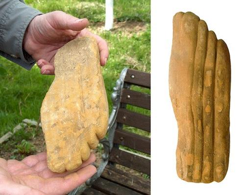 Una escultura de tamaño natural de piedra arenisca de un pie humano