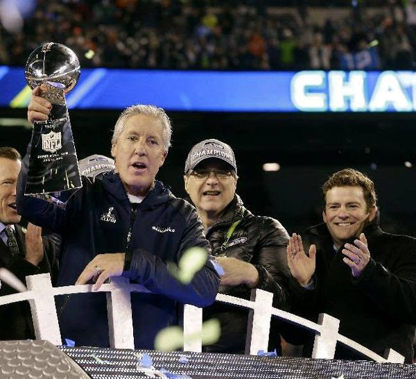 Seattle Seahawks coach Pete Carroll hoists up the Vince Lombardi Trophy after his team defeated the Denver Broncos, 43-8, in Super Bowl XLVIII...on February 2, 2014.