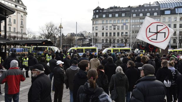 Counter-demonstrators gather to show their disapproval of an anti-migrant demonstration at  Norrmalmstorg Square in ...