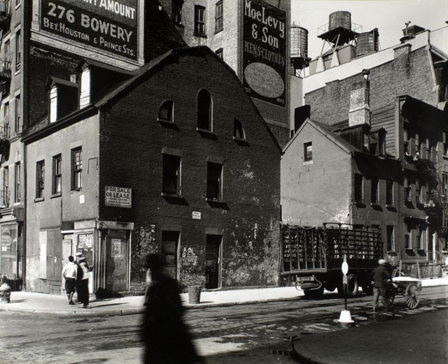 Mulberry and Prince Streets, Manhattan. Building with gambrel roof, dormers on corner, small houses along street where man pushes cart, large buildings topped with water towers beyond.