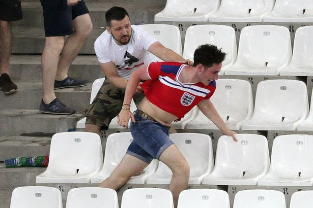 Russian fan grabs hold of an English supporter who then proceeds to rip it off his back and taunt him with it