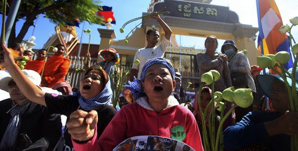 Protesters holding lotuses shout during demonstration, calling Cambodia's National Assembly to release peaceful protesters who have been detained, in Phnom Penh
