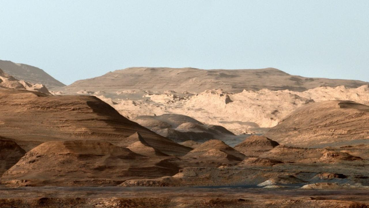 This composite, false-color image of Mount Sharp inside Gale crater on Mars shows geologists a changing planetary environment. On Mars, the sky is not blue, but the image was made to resemble Earth so that scientists could distinguish stratification layers. Image credit: NASA/JPL
