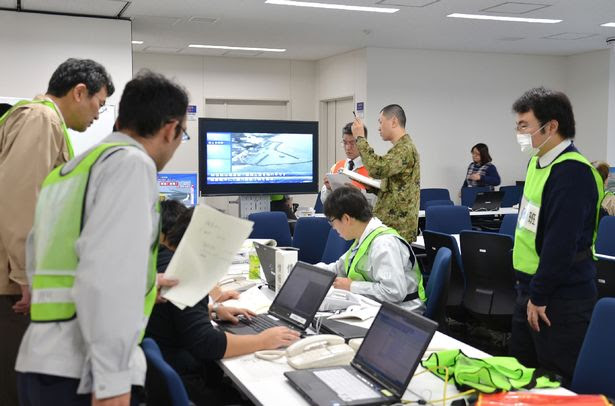 Officers at the Fukushima prefectural office gather data following an earthquake