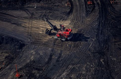 A bucket loader digs for oil sands at a mine in this aerial photograph taken near Fort McMurray, Alberta, Canada, on June 4, 2015.