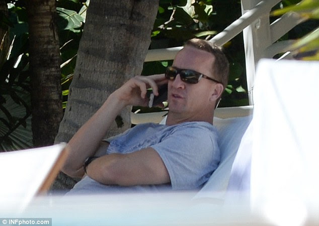 When business calls: Manning was also spotted making phone calls out of the water, while admiring his wife Ashley's beach-ready body
