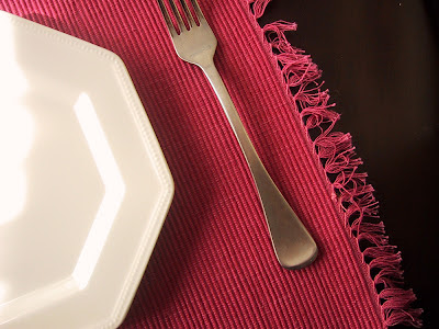 Dinner plate and a fork on a pink woven place mat.