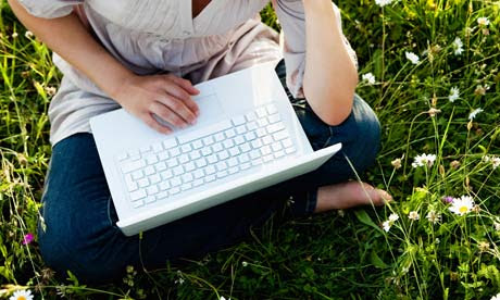 Woman with laptop in wild meadow