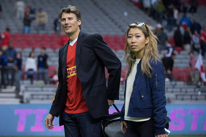 Vancouver Mayor Gregor Robertson, left, and singer-songwriter Wanting Qu leave the field after Robertson presented the man of the match award after Canada and Japan played a rugby test match in Vancouver, B.C., on Saturday June 11, 2016. (Darryl Dyck/CP)