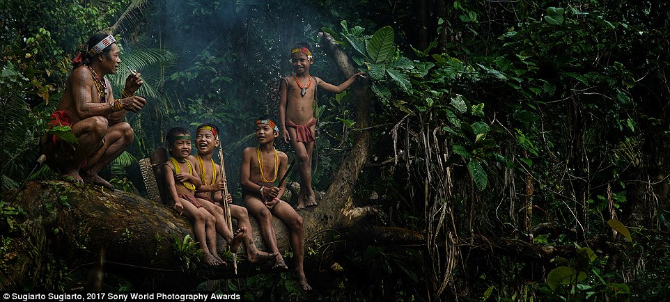 In the jungle of Sumatra Barat, Indonesia, children share a joke with an elder of the Mentawai Tribe on Mentawai Island