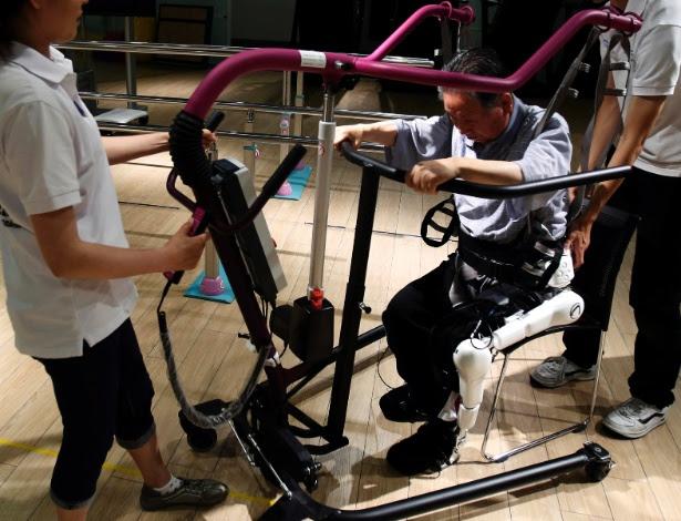 Tasuku Takahashi, 82, um dos usuários da companhia de robôs Cyberdyne (Hybrid Assistive Limb) e cujo corpo ficou paralisado devido a um problema cerebral, tenta se levantar utilixando um exotraje durante treinamento no estúdio da empresa em Tsukuba, ao norte de Tóquio. O Japão possui a maior população de robôs