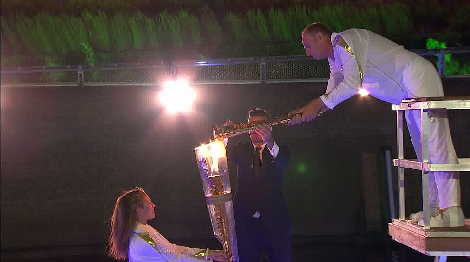 The flame is passed to five times gold medal winner Sir Steve Redgrave by David Beckham, who carried the flame into Stratford on a speedboat