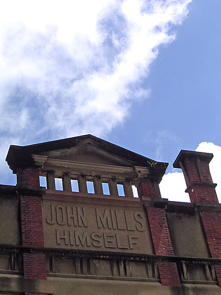 photo - building facade with John Mills Himself written in the render
