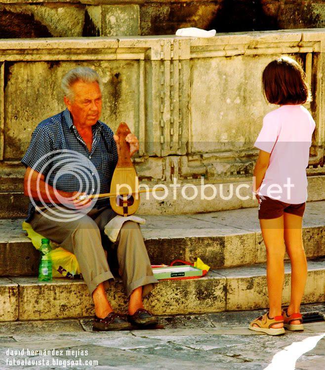 Un viejo músico toca un instrumento tradicional de cuerda mientras una niña observa