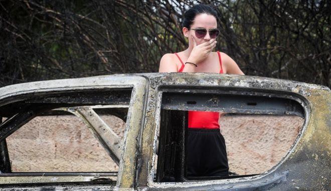 Γυναίκα στέκεται σαστισμένη μπροστά από καμένο αυτοκίνητο στο Μάτι Αττικής