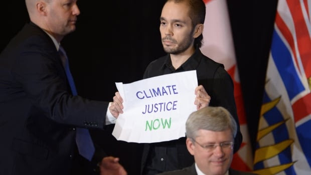 Sean Devlin, a climate change protester, holds a sign reading 'Climate justice now' during an event with Prime Minister Stephen Harper at the Vancouver Board of Trade on Jan. 6, 2013.