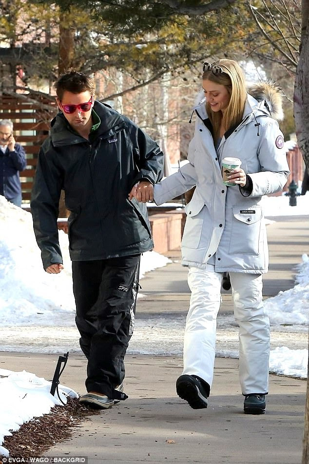 Elle covered up her statuesque form with plus white snow pants and a matching jacket with a fur-lined hood