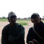 Dois Xavante participam de reunião. Ao fundo, as ocas da aldeia.