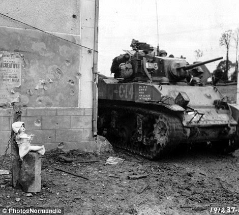Surreal: A doll posed against the concrete post as an enormous American M5A1 tank from the 3rd Armored Division drives past