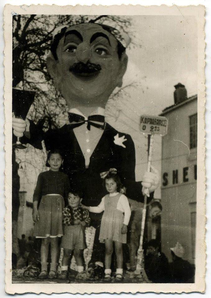 """1955, δεύτερη χρονιά του Καλυβιανού Καρναβαλιού! Αυτή τη χρονιά ο καρνάβαλος ήταν """"εισαγόμενος""""... Το κεφάλι είχε έρθει με πακέτο από την Πάτρα και το σώμα κατασκευάστηκε με εφημερίδες και αλευρόκολα... Το αμαξίδιο τώρα δεν το τράβαγε άνθρωπος αλλά δύο γαϊδουράκια. Σαφώς βελτιωμένος από τον πρώτο…. Στη φωτογραφία ο Χαράλαμπος Αθηναίου με τα παιδιά του Αγγελική, Ευάγγελος και Αμαλία"""
